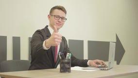 Νέο όμορφο άτομο πορτρέτου στην επίσημη ένδυση και γυαλιά που δακτυλογραφούν σε ένα lap-top και που παρουσιάζουν αντίχειρα επάνω  απόθεμα βίντεο