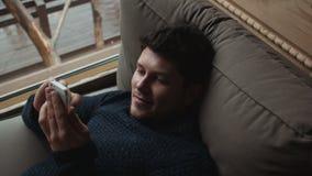 Νέο όμορφο άτομο που κάνει σερφ στο διαδίκτυο στο smartphone του στο σπίτι φιλμ μικρού μήκους