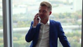 Νέο όμορφο άτομο που μιλά στο τηλέφωνο υπερασπιμένος το παράθυρο απόθεμα βίντεο