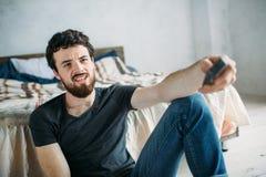 Νέο όμορφο άτομο που προσέχει τη TV σε ένα πάτωμα στο σπίτι Στοκ Εικόνες