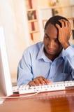 Νέο όμορφο άτομο που φορά την μπλε συνεδρίαση πουκάμισων γραφείων από τον υπολογιστή που κλίνει επάνω στο γραφείο δακτυλογραφώντα Στοκ Φωτογραφία