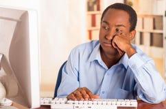 Νέο όμορφο άτομο που φορά την μπλε συνεδρίαση πουκάμισων γραφείων από τον υπολογιστή που κλίνει επάνω στο γραφείο δακτυλογραφώντα Στοκ Εικόνες