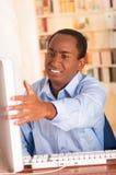 Νέο όμορφο άτομο που φορά την μπλε συνεδρίαση πουκάμισων γραφείων από τον υπολογιστή που κάνει τις χειρονομίες χεριών και που εξε Στοκ Εικόνες