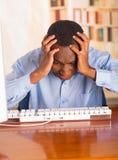 Νέο όμορφο άτομο που φορά την μπλε συνεδρίαση πουκάμισων γραφείων από τον υπολογιστή που κλίνει προς τα εμπρός πέρα από το κεφάλι Στοκ Εικόνες