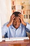Νέο όμορφο άτομο που φορά την μπλε συνεδρίαση πουκάμισων γραφείων από τον υπολογιστή που κλίνει προς τα εμπρός πέρα από το κεφάλι Στοκ Φωτογραφίες
