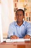Νέο όμορφο άτομο που φορά την μπλε συνεδρίαση πουκάμισων γραφείων από το γραφείο υπολογιστών που δακτυλογραφεί και που φαίνεται χ Στοκ φωτογραφίες με δικαίωμα ελεύθερης χρήσης