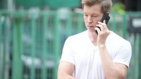 Νέο όμορφο άτομο που χρησιμοποιεί το κινητό τηλέφωνο στις οδούς υπαίθρια απόθεμα βίντεο