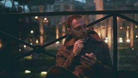 Νέο όμορφο άτομο που χρησιμοποιεί το smartphone, που εξισώνει την πόλη σε ένα υπόβαθρο Το άτομο κοιτάζει βιαστικά το Διαδίκτυο με Στοκ φωτογραφία με δικαίωμα ελεύθερης χρήσης