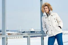 Νέο όμορφο άτομο σε ένα άσπρο σακάκι με την κουκούλα γουνών το χειμώνα Σιβηρία πορτρέτο μόδας στοκ φωτογραφία με δικαίωμα ελεύθερης χρήσης