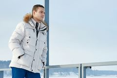 Νέο όμορφο άτομο σε ένα άσπρο σακάκι με την κουκούλα γουνών το χειμώνα Σιβηρία πορτρέτο μόδας στοκ εικόνα
