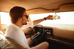 Νέο όμορφο άτομο στα γυαλιά ηλίου που κάθεται μέσα στο αυτοκίνητό του στοκ εικόνα