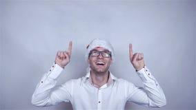 Νέο όμορφο άτομο στο άσπρο καπέλο πουκάμισων και santa που παρουσιάζει διάστημα αντιγράφων ανωτέρω απόθεμα βίντεο
