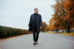 Νέο όμορφο άτομο στο παλτό Μοντέρνη καλά ντυμένη τοποθέτηση ατόμων στο μοντέρνο παλτό Βέβαιο και αγόρι υπαίθριο στο φθινόπωρο στοκ εικόνα