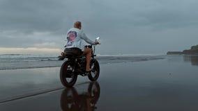 Νέο όμορφο άτομο hipster που οδηγά το σύγχρονο δρομέα μοτοσικλετών συνήθειας στη μαύρη παραλία άμμου κοντά στο νερό Κάνοντας σερφ φιλμ μικρού μήκους