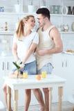 Νέο όμορφο αγαπώντας ζεύγος που κατασκευάζει το φρέσκο χυμό από πορτοκάλι και που έχει τη διασκέδαση στην κουζίνα Στοκ Εικόνα