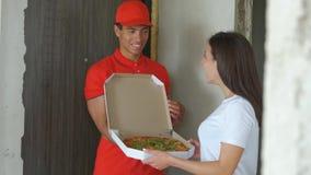 Νέο όμορφο αγόρι παράδοσης πιτσών Όμορφη αποκτημένη κορίτσι πίτσα τρόφιμα παράδοσης έννοιας απόθεμα βίντεο
