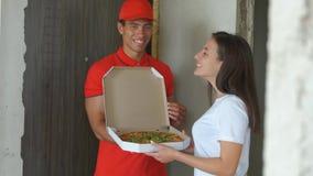 Νέο όμορφο αγόρι παράδοσης πιτσών Όμορφη αποκτημένη κορίτσι πίτσα τρόφιμα παράδοσης έννοιας φιλμ μικρού μήκους