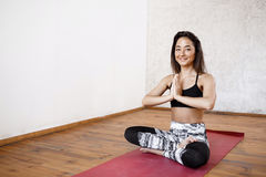 Νέο όμορφο αθλητικό κορίτσι που ασκεί την εσωτερική συνεδρίαση γιόγκας σε Ardha Padmasana με τη χειρονομία Namaste φοινικών, μισό Στοκ Εικόνες