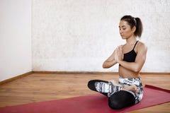 Νέο όμορφο αθλητικό κορίτσι που ασκεί την εσωτερική συνεδρίαση γιόγκας σε Ardha Padmasana με τους φοίνικες σε Namaste, μισό Lotus Στοκ Εικόνες