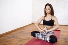 Νέο όμορφο αθλητικό κορίτσι που ασκεί την εσωτερική συνεδρίαση γιόγκας σε Ardha Padmasana, μισή στάση Lotus Στοκ Φωτογραφίες