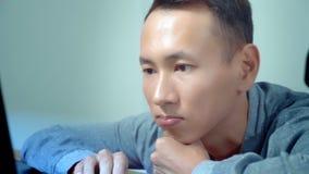 Νέο όμορφο ασιατικό άτομο που χρησιμοποιεί το lap-top του, που κάθεται στο γραφείο στην αρχή φιλμ μικρού μήκους