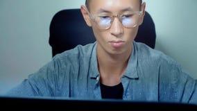 Νέο όμορφο ασιατικό άτομο που χρησιμοποιεί το lap-top του, που κάθεται στο γραφείο στην αρχή στοκ εικόνες