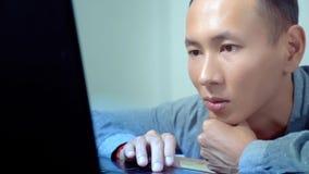 Νέο όμορφο ασιατικό άτομο που χρησιμοποιεί το lap-top του, που κάθεται στο γραφείο στην αρχή στοκ φωτογραφία με δικαίωμα ελεύθερης χρήσης