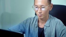 Νέο όμορφο ασιατικό άτομο που χρησιμοποιεί το lap-top του, που κάθεται στο γραφείο στην αρχή στοκ φωτογραφίες με δικαίωμα ελεύθερης χρήσης