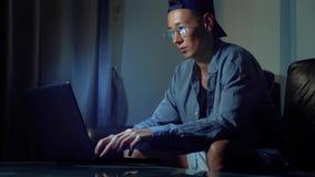 Νέο όμορφο ασιατικό άτομο στα γυαλιά με τις αντανακλάσεις που χρησιμοποιούν το lap-top του, που κάθεται το βράδυ στο δωμάτιο Στο  στοκ εικόνα