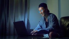 Νέο όμορφο ασιατικό άτομο στα γυαλιά με τις αντανακλάσεις που χρησιμοποιούν το lap-top του, που κάθεται το βράδυ στο δωμάτιο Στο  στοκ φωτογραφία