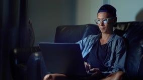 Νέο όμορφο ασιατικό άτομο στα γυαλιά με τις αντανακλάσεις που χρησιμοποιούν το lap-top του, που κάθεται το βράδυ στο δωμάτιο Στο  στοκ εικόνες με δικαίωμα ελεύθερης χρήσης