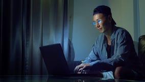 Νέο όμορφο ασιατικό άτομο στα γυαλιά με τις αντανακλάσεις που χρησιμοποιούν το lap-top του, που κάθεται το βράδυ στο δωμάτιο Στο  στοκ φωτογραφίες με δικαίωμα ελεύθερης χρήσης
