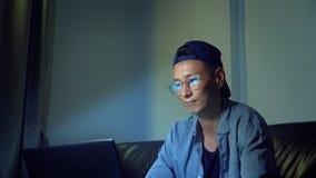 Νέο όμορφο ασιατικό άτομο στα γυαλιά με τις αντανακλάσεις που χρησιμοποιούν το lap-top του, που κάθεται το βράδυ στο δωμάτιο Στο  στοκ φωτογραφίες