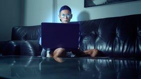 Νέο όμορφο ασιατικό άτομο στα γυαλιά με τις αντανακλάσεις που χρησιμοποιούν το lap-top του, που κάθεται το βράδυ στο δωμάτιο Στο  στοκ εικόνες