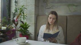 Νέο, όμορφο βιβλίο ανάγνωσης κοριτσιών στον καφέ φιλμ μικρού μήκους
