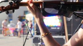 Νέο όμορφο βιολί παιχνιδιών γυναικών πλάγιας όψης κινηματογραφήσεων σε πρώτο πλάνο φιλμ μικρού μήκους