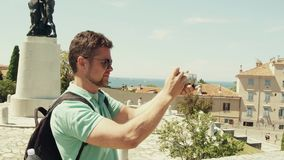 Νέο όμορφο γενειοφόρο άτομο που κάνει τις υπαίθριες φωτογραφίες με τη συμπαγή κάμερα του Στοκ Εικόνες