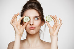 Νέο όμορφο γυμνό κρύβοντας μάτι χαμόγελου κοριτσιών πίσω από τη φέτα αγγουριών πέρα από το άσπρο υπόβαθρο Beauty spa και cosmetol Στοκ Εικόνες