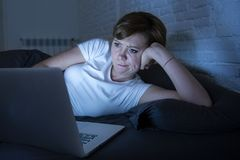 Νέο όμορφο Διαδίκτυο έθισε την άϋπνη και κουρασμένη γυναίκα που εργάζεται στο lap-top στο κρεβάτι αργά τη νύχτα Στοκ Εικόνες