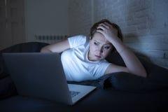 Νέο όμορφο Διαδίκτυο έθισε την άϋπνη και κουρασμένη γυναίκα που εργάζεται στο lap-top στο κρεβάτι αργά τη νύχτα Στοκ Φωτογραφίες