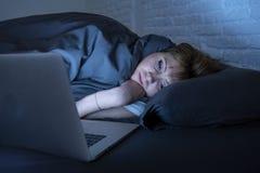Νέο όμορφο Διαδίκτυο έθισε την άϋπνη και κουρασμένη γυναίκα που εργάζεται στο lap-top στο κρεβάτι αργά τη νύχτα Στοκ εικόνες με δικαίωμα ελεύθερης χρήσης