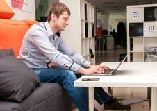 Νέο όμορφο ευτυχές άτομο με τον υπολογιστή στο γραφείο Στοκ Εικόνα
