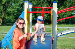Νέο όμορφο ευτυχές οικογενειακό παιχνίδι κοριτσάκι μητέρων και κορών στην ταλάντευση, και γύρος στο χαμόγελο λούνα παρκ Στοκ φωτογραφία με δικαίωμα ελεύθερης χρήσης