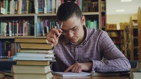 Νέο όμορφο εφηβικό άτομο που φορά τα γυαλιά που κάθονται στον πίνακα στην πανεπιστημιακή σκέψη βιβλιοθηκών πέρα από τους υπολογισ απόθεμα βίντεο