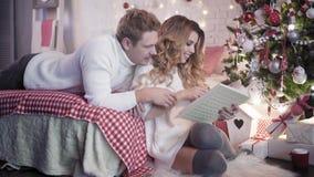 Νέο όμορφο ζεύγος που εξετάζει το λεύκωμα φωτογραφιών κοντά στο χριστουγεννιάτικο δέντρο φιλμ μικρού μήκους