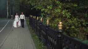 Νέο όμορφο ζεύγος που περπατά μέσω του πάρκου στη ημέρα γάμου τους απόθεμα βίντεο