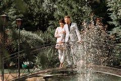 Νέο όμορφο ζεύγος που περπατά στο πάρκο και τις στάσεις στη γέφυρα Στοκ Φωτογραφίες
