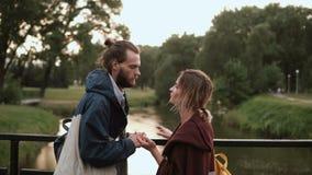 Νέο όμορφο ζεύγος που περπατά στο πάρκο στο ηλιοβασίλεμα Μοντέρνοι άνδρας και γυναίκα που στέκονται στη γέφυρα και την ομιλία απόθεμα βίντεο