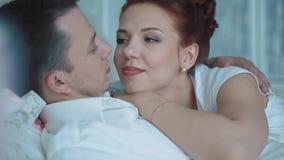 Νέο όμορφο ζεύγος που στηρίζεται στο κρεβάτι, που εξετάζει την απόσταση, κινηματογράφηση σε πρώτο πλάνο απόθεμα βίντεο