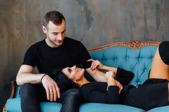 Νέο όμορφο ζεύγος στα σκοτεινά ενδύματα σε έναν τυρκουάζ εκλεκτής ποιότητας καναπέ Στοκ Εικόνα